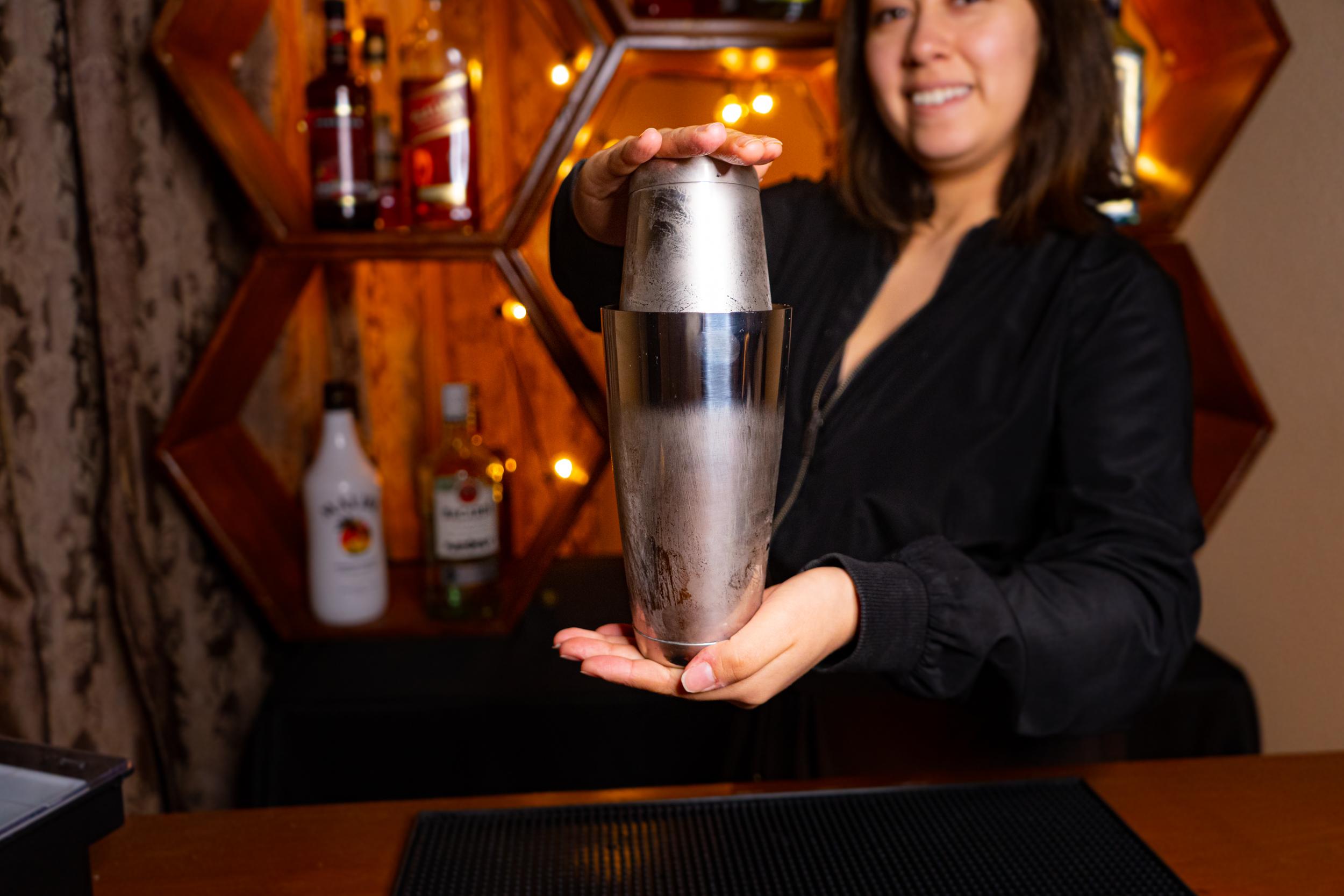 a female bartender holding Boston Shaker